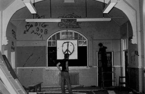 Andy Gibson with Booga, painting the fire exit sign, at The Bunker, Green Terrace, 1982