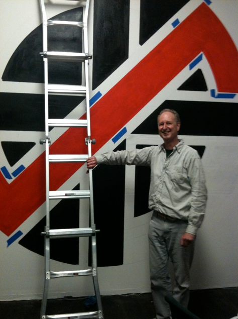 Dave King - stood in front of a recent wall size version of the Crass symbol